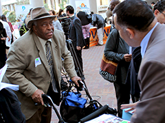 An applicant approaches the booth of EWDD partner Coalition for Responsible Community Development (CRCD) at the job fair
