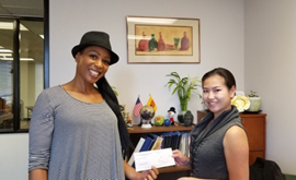 Local entrepreneur Enjunaya Canton (left) accepting her $500 microloan from the Mid-City LA BusinessSource Center