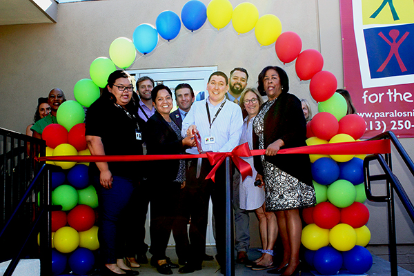 Jorge Orozco, Director of PLN Youth Workforce Services, cuts the ribbon at the grand opening of the PLN Westlake/MacArthur YouthSource Center