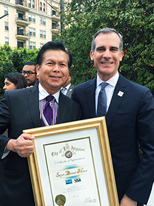 Glady Uy, owner of Hollywood's Super Donut House, receives a Certificate of Appreciation by LA Mayor Eric Garcetti at the 2018 Los Angeles Small Business Week