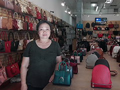 Local entrepreneur Jenny Chih poses on the floor of her business, JC Handbags, located in the fashion district of downtown LA