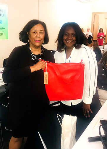 EWDD General Manager Jan Perry, left, poses with handbag designer Lavena and one of her products, a red leather handbag. The South LA BSC gave her a grant to buy a sewing machine for her business.