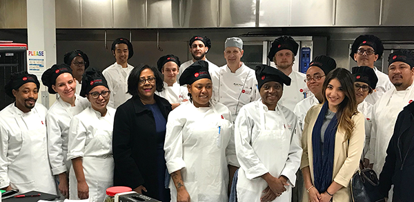 EWDD General Manager Jan Perry (front row, fourth from left) poses with LAHTA instructor Chef Mitchell Frieder (back row, center) and current Culinary Apprenticeship Program students