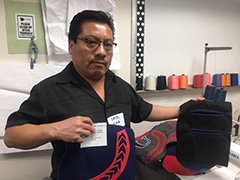 Zaul Pena displays his high-end samples, created from the training he received in the Stitches program