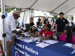 EWDD staff offer YouthSource, WorkSource and BusinessSource service information to a 2019 Central Avenue Jazz Fest attendee