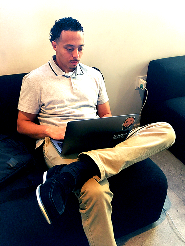 Compass Rose Collaborative alum Demarkus Matthews working on a laptop for his information technology industry job with General Assembly