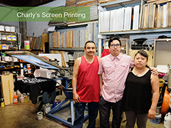 "Carlos ""Charly"" Flores poses inside his family owned business, Charly's Screen Printing, with his mother and father"
