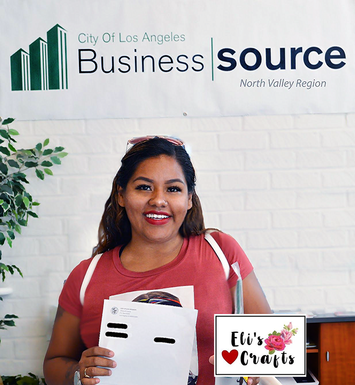 Elizabeth Rojas, owner of Eli's Crafts, shows off her City of LA business license that the North Valley BusinessSource Center helped her obtain