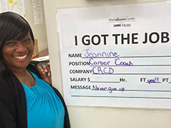"Jeannine poses next to the ""Just Hired"" notice board announcing her new job as a WorkSource Career Coach"