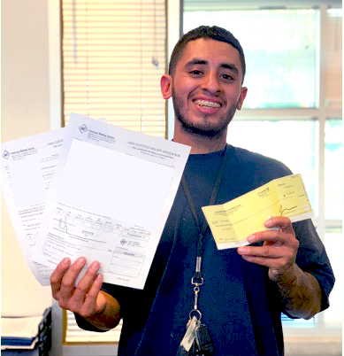 Compass Rose Collaborative participant Juan poses with the welding certificates he earned after completing a 16-week American Welding Society program