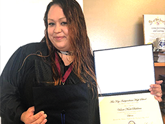 LA:RISE program participant Valorie poses in cap and gown after earning her GED