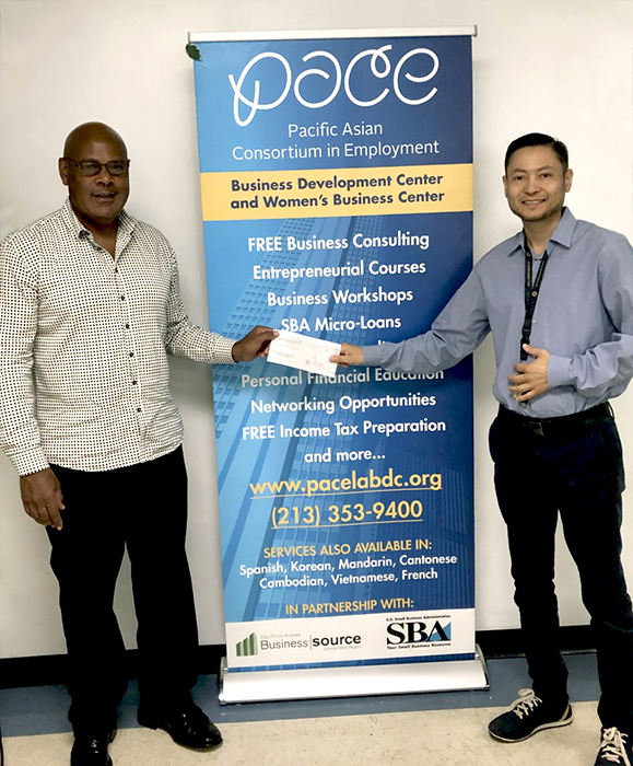 Entrepreneur Lennie Brown (left) holds $4,500 microloan check that he obtained with assistance from the PACE operated Central/West BusinessSource Business Counselor Frank Sosa (right)