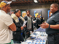Job seekers (left) speak with a potential employer at the Southeast Los Angeles WorkSource Center job fair May 2, 2019