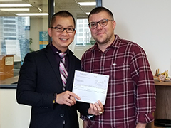 Mid-City Region BusinessSource loan counselor Phong Le (left) hands local business owner Sam Rypinski (right) obtain a $125,000 SBA loan to expand Riverside Studios, LLC