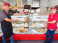 Maria Lopez (right) stands proudly in front of her new pastry display case in Todos Los Pastelitos Caseros, her family-owned bakery and coffee shop located in Panorama City