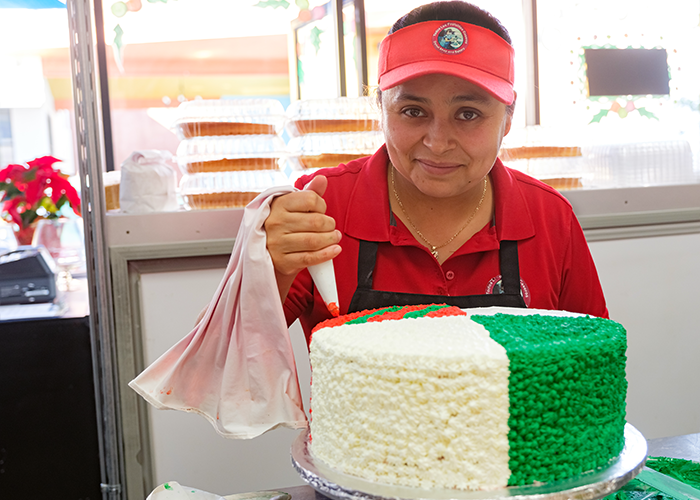 Maria Lopez decorates a custom cake at Todos Los Pastelitos Caseros, her family-owned bakery and coffee shop located in Panorama City
