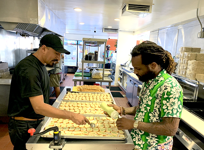 Entrepreneur Peace Love Reedburg (right) working in the kitchen of his Windsor Hills Grilled Fraiche restaurant location