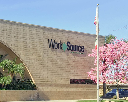 San Fernando Valley WorkSource Center with blossoming cherry tree, and California and United States Flags