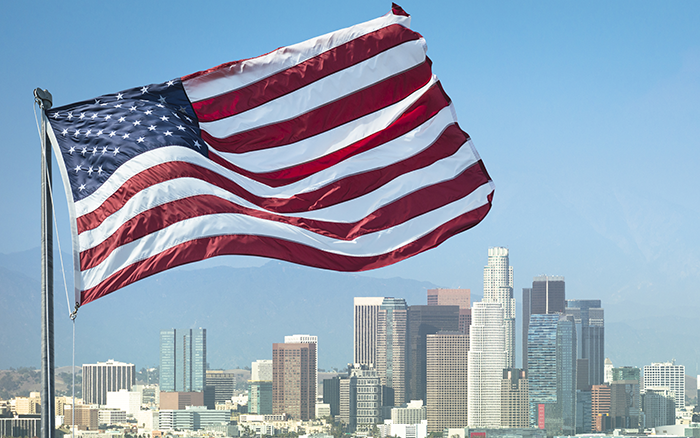 American Flag flying in fore-front with City of Los Angeles in background on sunny day