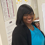 LA:RISE participant Jeannine poses next to the Just Hired notice board announcing her new job as a WorkSource Career Coach