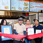 Owner Genaro Rodriguez (center) at the grand opening of his restuarant 3 Hermanos Kitchen
