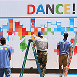 Watts YouthSource participants working to improve their neighborhood by painting a vibrant mural with a positive message