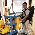 Matias Vanegas, owner of American Cleaning Company, cleans an office hallway